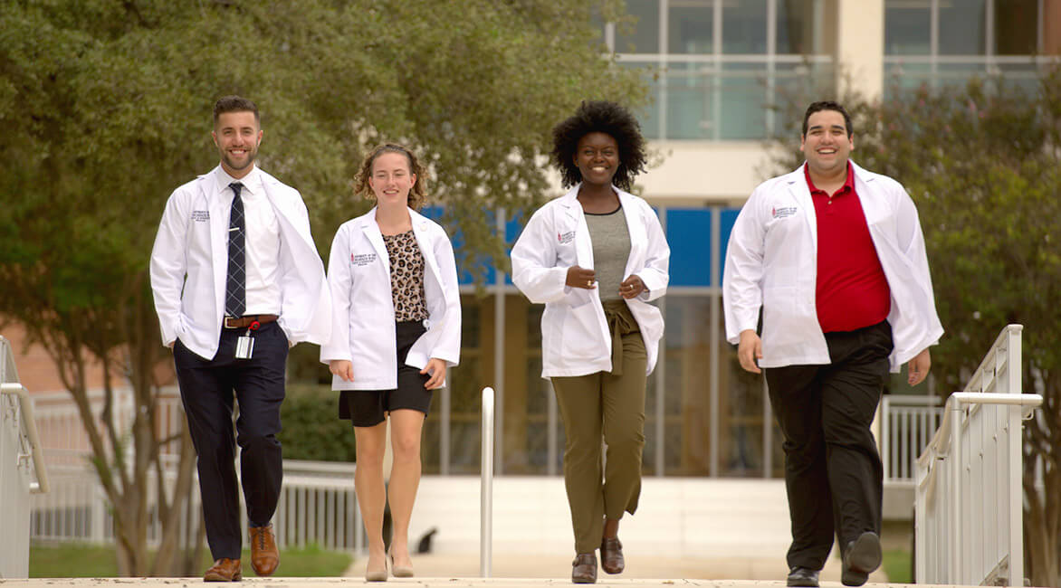 UIW school of osteopathic medicine students walking in a row in front of the building