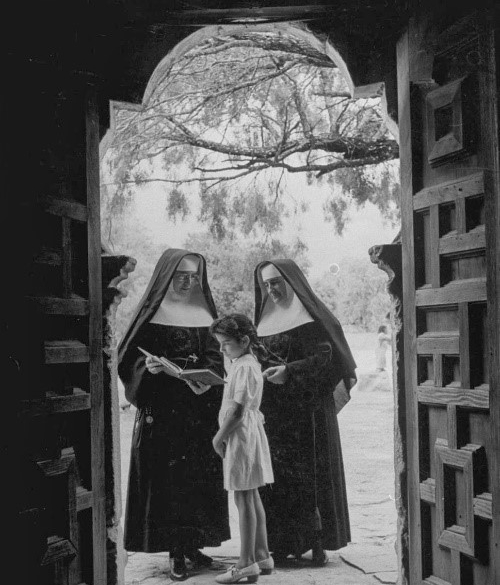 CCVI sisters black and white image, standing in a doorway with a child.