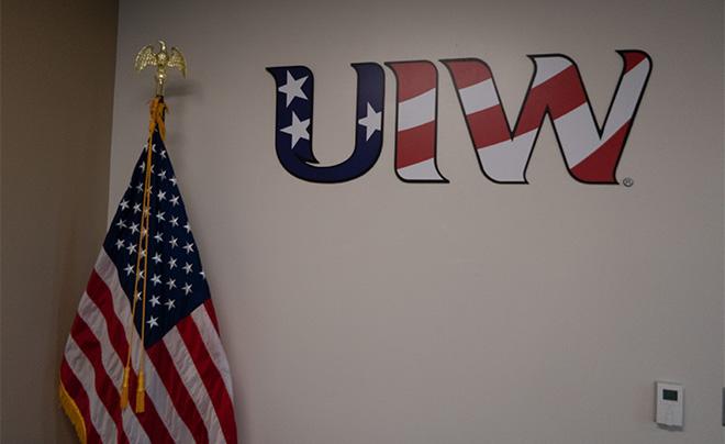 UIW log and an American flag